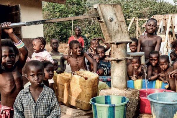 Ragazzi e donne di un villaggio in Sierra Leone che collaudano un pozzo