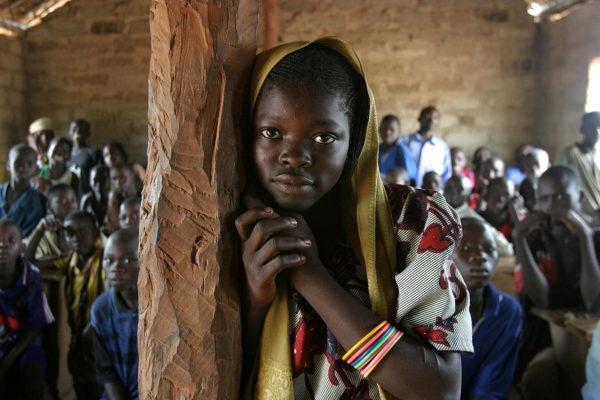 Primo piano di ragazza congolese appoggiata ad un palo di legno, in una stanza piena di persone